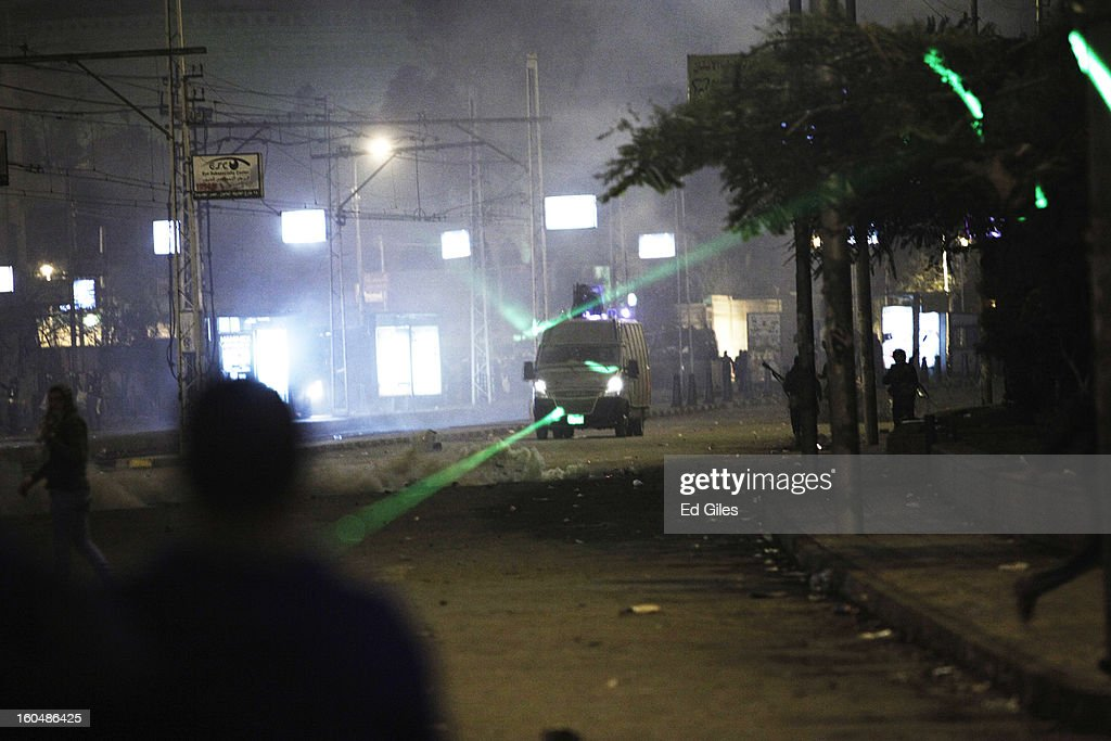 An Egyptian armored riot police van of the Central Security Forces is lit up by laser pointers used by protesters during clashes outside the Egyptian Presidential Palace in the suburb of Heliopolis on February 1, 2013 in Cairo, Egypt. Protests continued across Egypt nearly one week after the second anniversary of the Egyptian Revolution that overthrew former President Hosni Mubarak on January 25, 2011. Further protests are expected over the weekend to commemorate the first anniversary of the Port Said football massace, when over 70 fans of the Cairo-based Al Ahly football club were killed in a violent post-match brawl between fans of the opposing teams inside the Port Said football stadium after a match between the Al Ahly and Al Masry football teams. (Photo by Ed Giles/Getty Images).