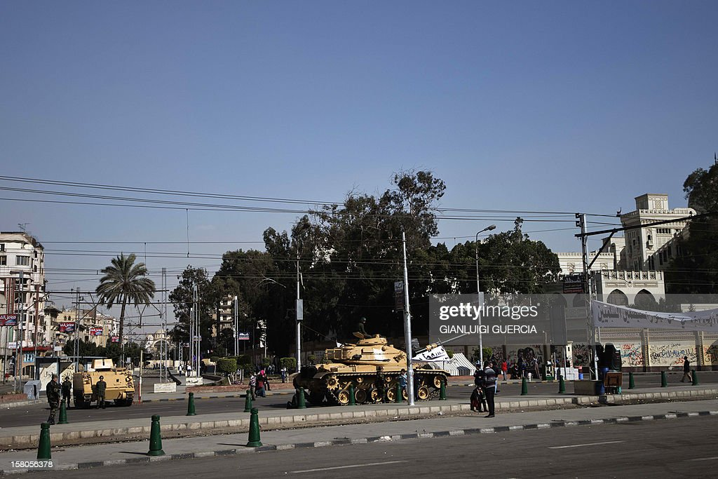 An Egyptian armoured personnel carrier (APC) and tank are deployed outside the presidential palace in Cairo on December 10, 2012. President Mohamed Morsi has ordered Egypt's army to 'cooperate' with police and given it powers of arrest until the results of a referendum to be held this weekend, according to a decree obtained by AFP. AFP PHOTO/GIANLUIGI GUERCIA