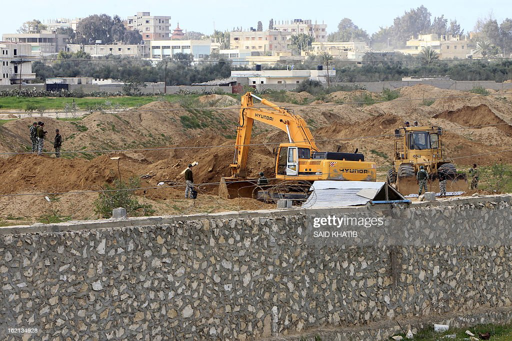 An Egyptian army bulldozer destroys smuggling tunnels along the border with Gaza, in the southern Gaza Strip on February 19, 2013. Gaza's Hamas rulers have closed hundreds of tunnels running under the territory's border with Egypt due to health concerns over some smuggled items, an official said. The tunnels have been a vital lifeline for the flow of goods and fuel into the impoverished territory, which Israel has blockaded since 2006. AFP PHOTO / SAID KHATIB