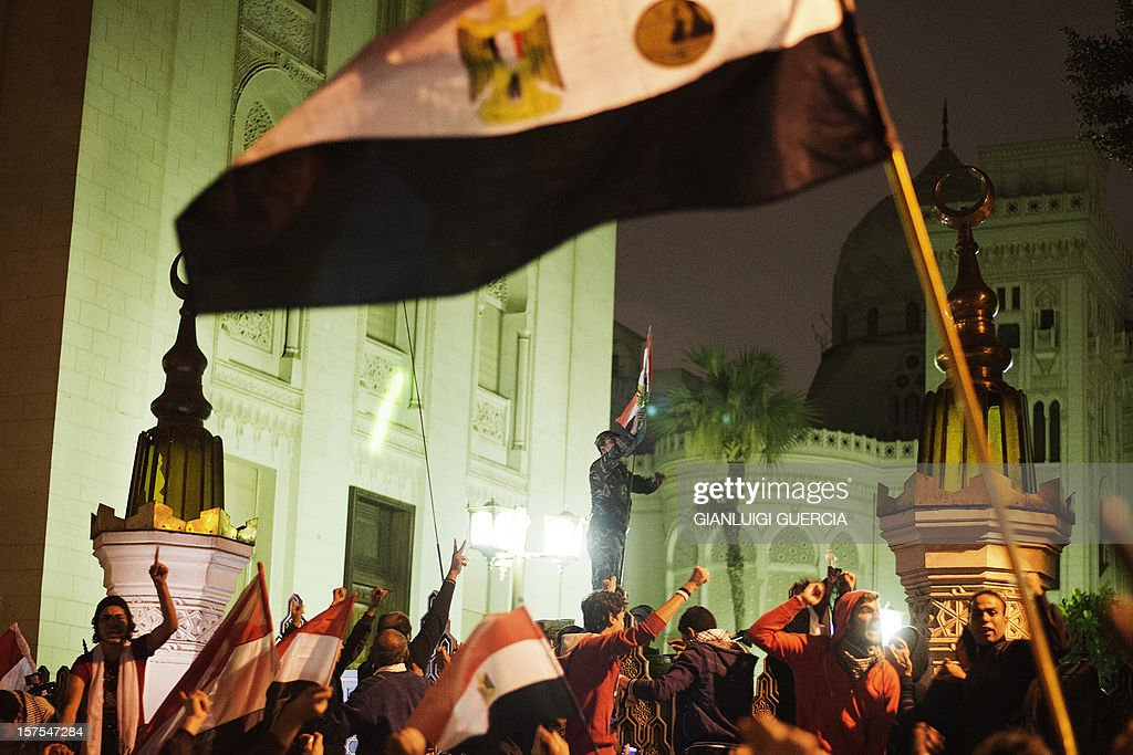 An Egyptian army soldier raises an egyptian flag as thousands of demonstrators protest outside the Egyptian presidential palace on December 4, 2012 in Cairo. Tens of thousands of demonstrators encircled the presidential palace after riot police failed to keep them at bay with tear gas, in a growing crisis over President Mohamed Morsi's decree widening his powers. AFP PHOTO/GIANLUIGI GUERCIA