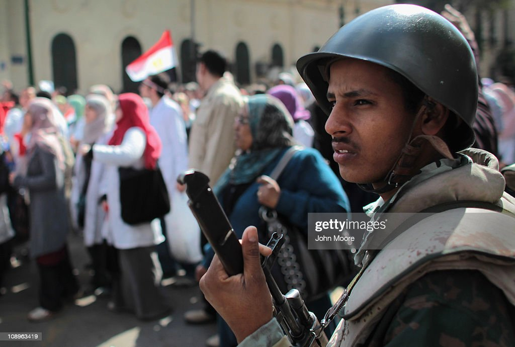 An Egyptian army soldier watches as doctors, medical workers and students march through Cairo to join anti-government protests in Tahrir Square on February 10, 2011 in Cairo, Egypt. Thousands of workers from different unions across Egypt, including many medical workers, have gone on strike, adding pressure on the government in the face of more than two weeks of protests calling for the resignation of President Hosni Mubarak.