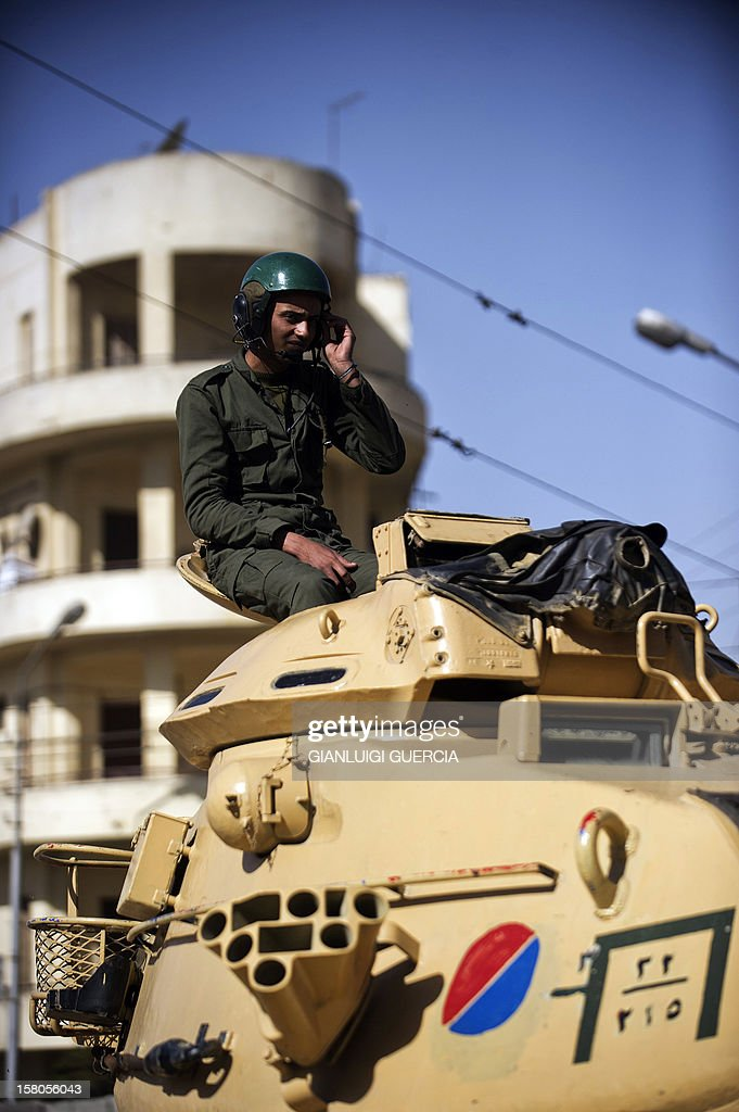 An Egyptian army soldiers sits on a tank deployed outside the presidential palace in Cairo on December 10, 2012. President Mohamed Morsi has ordered Egypt's army to 'cooperate' with police and given it powers of arrest until the results of a referendum to be held this weekend, according to a decree obtained by AFP. AFP PHOTO/GIANLUIGI GUERCIA