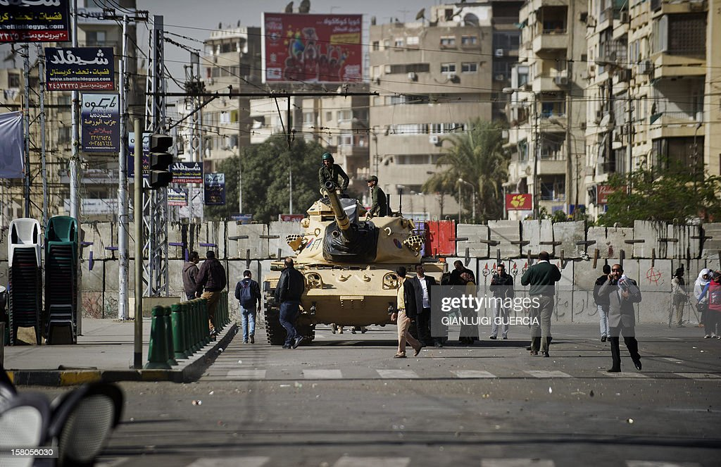 An Egyptian army tank is deployed near the presidential palace in Cairo as opposition supporters and people walk by on December 10, 2012. President Mohamed Morsi has ordered Egypt's army to 'cooperate' with police and given it powers of arrest until the results of a referendum to be held this weekend, according to a decree obtained by AFP.