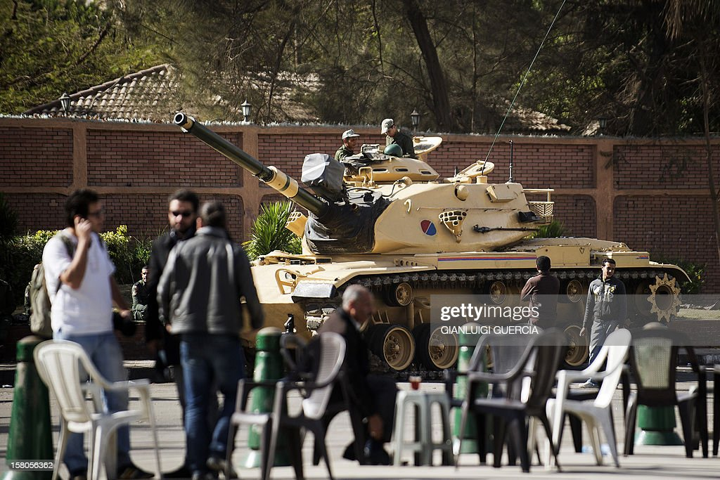 An Egyptian army tank is deployed outside the presidential palace in Cairo as opposition supporters and people walk by on December 10, 2012. President Mohamed Morsi has ordered Egypt's army to 'cooperate' with police and given it powers of arrest until the results of a referendum to be held this weekend, according to a decree obtained by AFP.