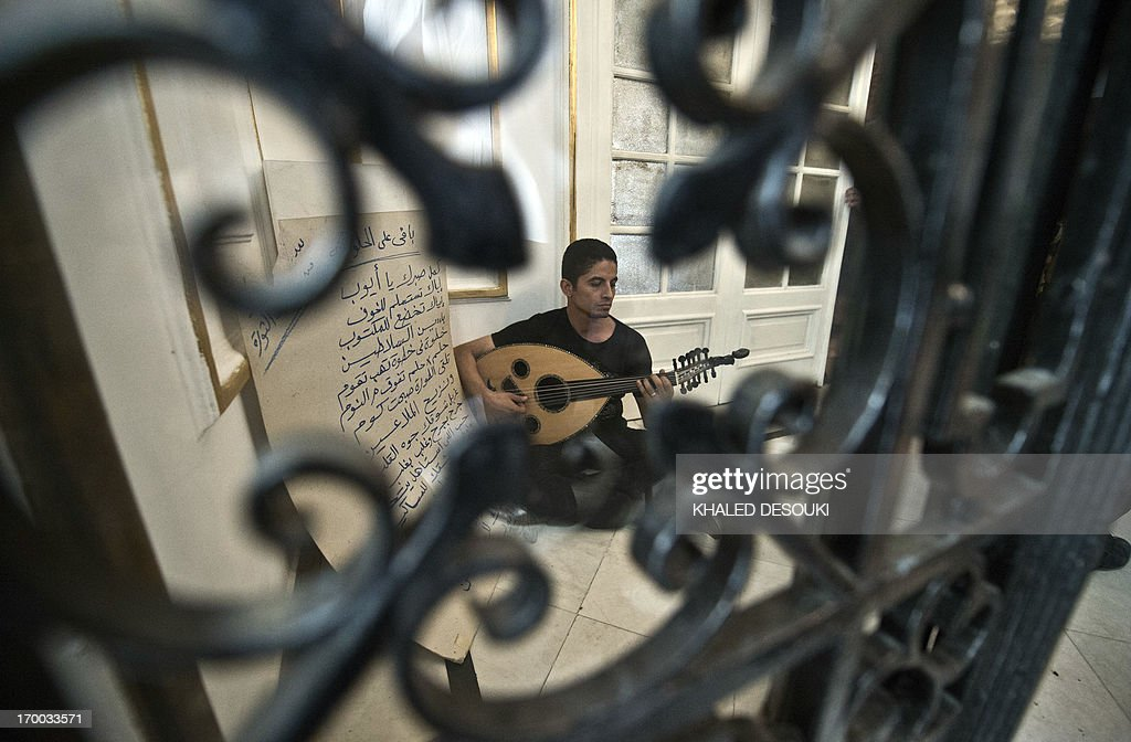 An Egyptian artist plays the Oud as demonstrators perform a sit-in at the office of culture minister, Alaa Abdelfattah, in Cairo on June 6, 2013, calling for his resignation.