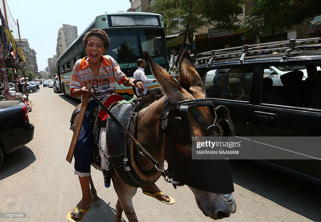 An Egyptian boy rides his donkey in a street in the working-class Saida Zeinab district of Cairo on the second day of the Muslim holy fasting month of Ramadan July 11, 2013. Many Egyptians are marking Ramadan, where Muslims abstain from eating and drinking from dawn to dusk, as uncertainty riddles the country amid soaring tension following last weeks' toppling of Islamist president Mohamed Morsi.