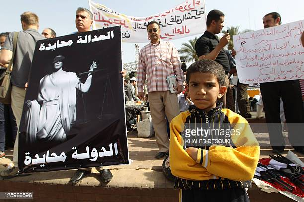 An Egyptian boy stands next to a protester holding a sign 'Impartial justice impartial state' as thousands of workers gather at Tahrir Square in...