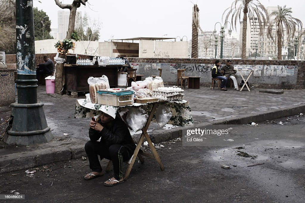 An Egyptian boy takes shelter from rain underneath a small tea stand during a protest against Egyptian President Mohammed Morsi in Tahrir Square on February 1, 2013 in Cairo, Egypt. Protests continued across Egypt nearly one week after the second anniversary of the Egyptian Revolution that overthrew former President Hosni Mubarak on January 25, 2011. Further protests are expected Friday to commemorate the first anniversary of the Port Said football massace, when over 70 fans of the Cairo-based Al Ahly football club were killed in a violent post-match brawl between fans of the opposing teams inside the Port Said football stadium after a match between the Al Ahly and Al Masry football teams. (Photo by Ed Giles/Getty Images).