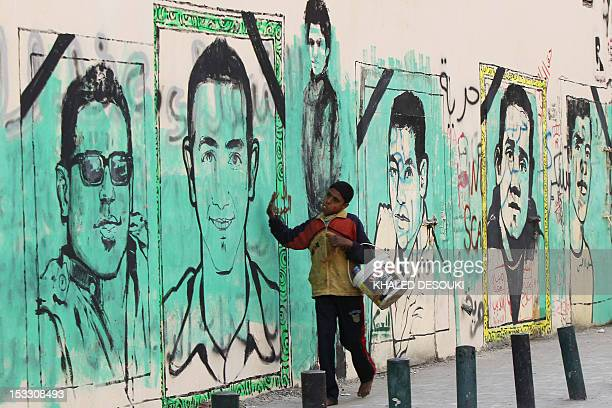 An Egyptian boy walks past graffiti depicting victims of the revolution near the interior ministry in Cairo on February 4 2012 Police fired tear gas...