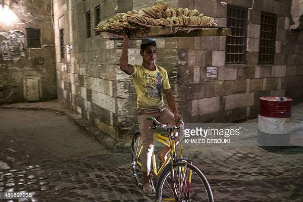 An Egyptian bread seller rides his bicycle as Muslim worshipers break the daylong fast during the holy month of Ramadan in Cairo Khan elKhalili...