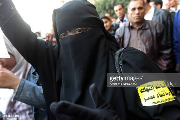 An Egyptian burqaclad woman with a sticker on her arm reading in Arabic 'I'm against the violation of Egyptian women's honour' takes part in a...