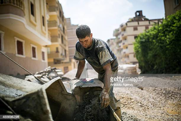 An Egyptian construction worker pours a cement sack to cement mixer in Al Mukaddem district of Cairo Egypt on September 10 2014 Egyptian...