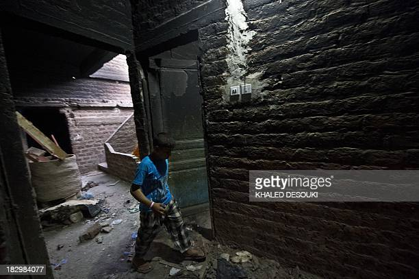 An Egyptian Coptic Christian boy walks inside his house that was damaged during an attack by Islamist men the previous month in the town of Delga in...