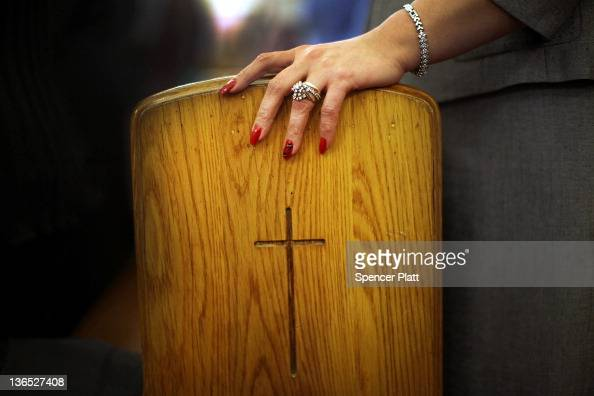 An Egyptian Coptic Christian women holds onto a pew during the celebration of Christmas Nativity Liturgy the start of Christmas at the Coptic...