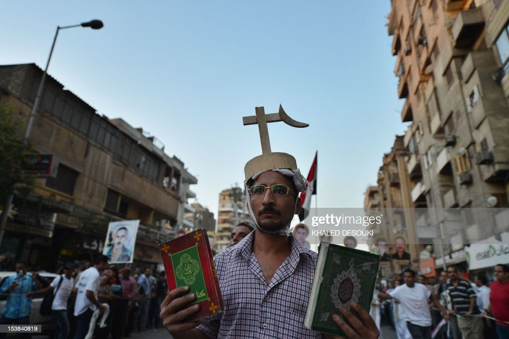 An Egyptian Coptic man holds a Bible and a Koran during a march in Cairo in Cairo on October 9, 2012 to mark one year since nearly 30 demonstrators were killed in a Coptic Christian demonstration that was violently crushed by security forces. On October 9, 2011, thousands of demonstrators marched from the neighborhood of Shubra to Maspero to denounce the torching of a church in the southern province of Aswan. The protest was attacked and violence flared when the army and riot police charged at the protesters, leaving 26 Coptic Christians, one Muslim man and one policeman dead, says Amnesty International.