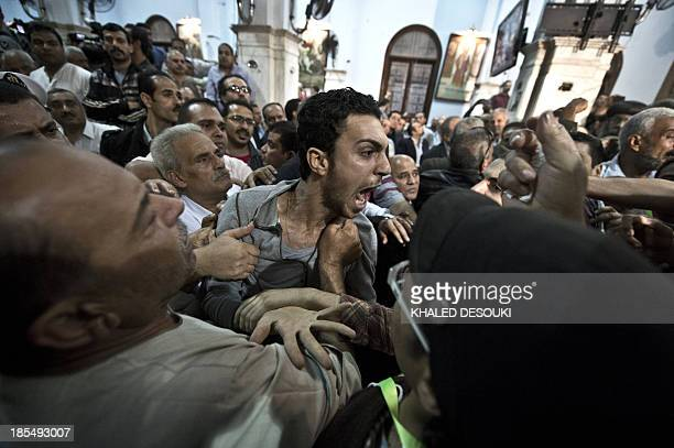 An Egyptian Coptic man reacts during the funeral service at the Virgin Mary Coptic Christian church of four victims gunned down as they attended a...