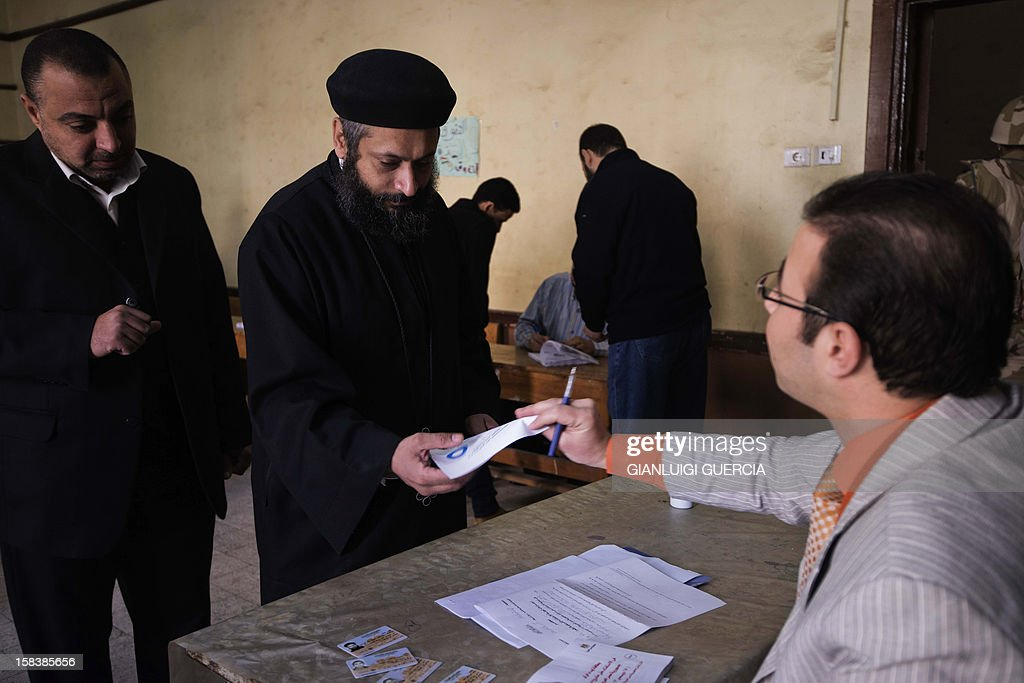 An Egyptian Coptic priest (C) arrives to cast his vote at a polling station in President Mohamed Morsi's hometown Zagazig in the Nile Delta on a new constitution supported by the ruling Islamists but bitterly contested by a secular-leaning opposition on December 15, 2012. Morsi's determined backing of the charter triggered the power struggle with the opposition, which is supported by judges who accuse the Islamists of overreaching.