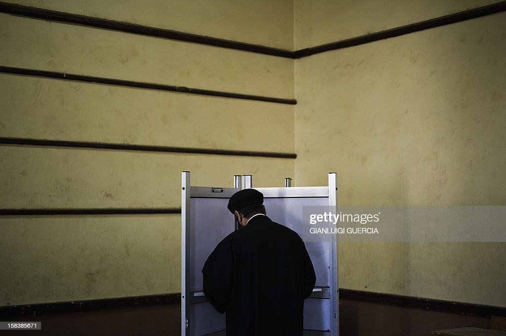 An Egyptian Coptic priest (R) proceeds to cast his vote at a polling station in President Mohamed Morsi's hometown Zagazig in the Nile Delta on a new constitution supported by the ruling Islamists but bitterly contested by a secular-leaning opposition on December 15, 2012. Morsi's determined backing of the charter triggered the power struggle with the opposition, which is supported by judges who accuse the Islamists of overreaching. AFP PHOTO/GIANLUIGI GUERCIA