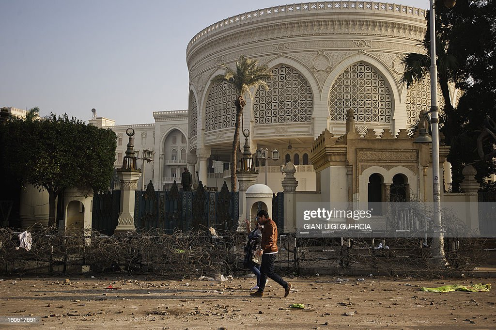 An Egyptian couple walks past a damaged barbed wire fence outside the presidential palace in Cairo on February 2, 2013 after a night of clashes between security forces and anti-government protesters. Egyptian riot police deployed near the presidential palace after a night of clashes between security forces and petrol-bomb throwing protesters that killed at least one man and wounded dozens.