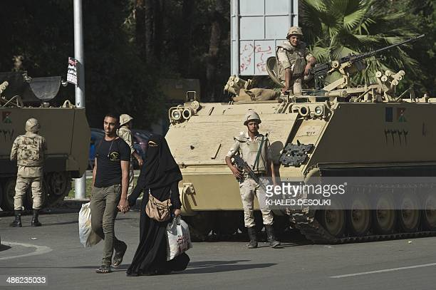 An Egyptian couple walks past an army tank as security forces stand guard outside Cairo University in the capital Cairo on April 23 2014 Student...