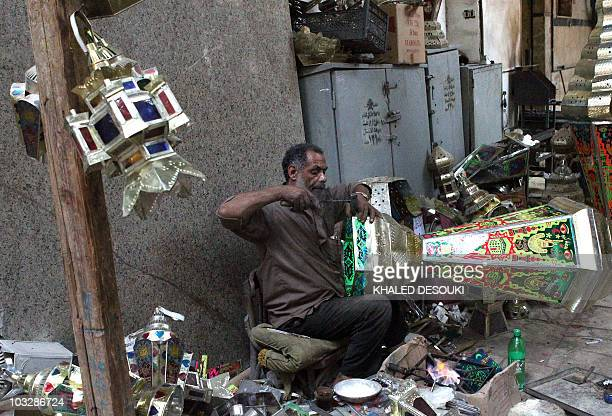 An Egyptian craftsman puts the final touches on a handmade lantern used during the Muslim holy fasting month of Ramadan at a workshop in downtown...