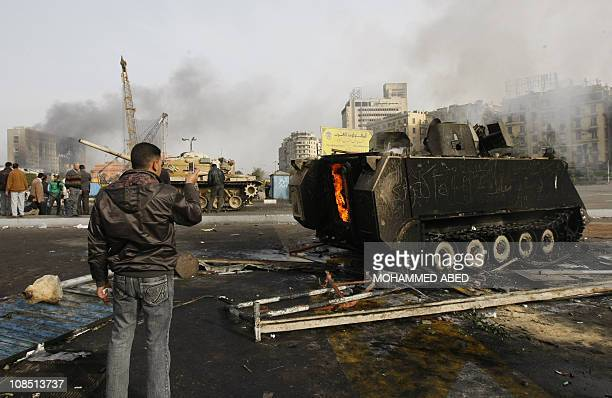 An Egyptian demonstrator uses his mobile phone to take a picture of a burnt army tank during clashes in central Cairo on January 29 2011 as thousands...