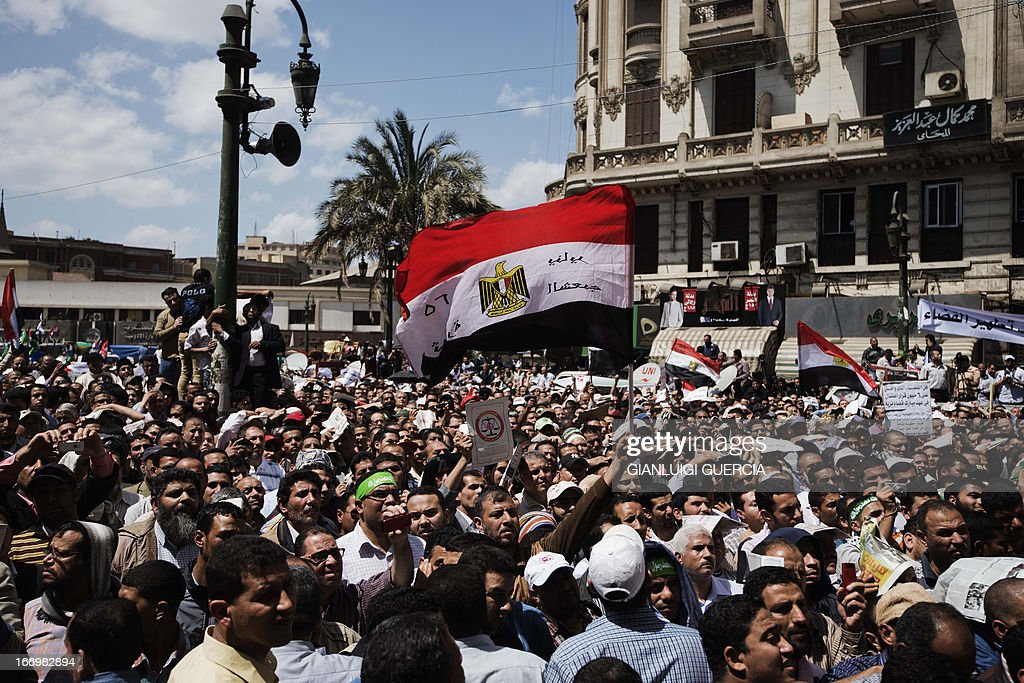 An Egyptian demonstrator waves his national flag as he attends a protest with Muslim Brotherhood supporters in front of the High Court in Cairo demanding a purge in the Egyptian judicial system on April 19, 2013.