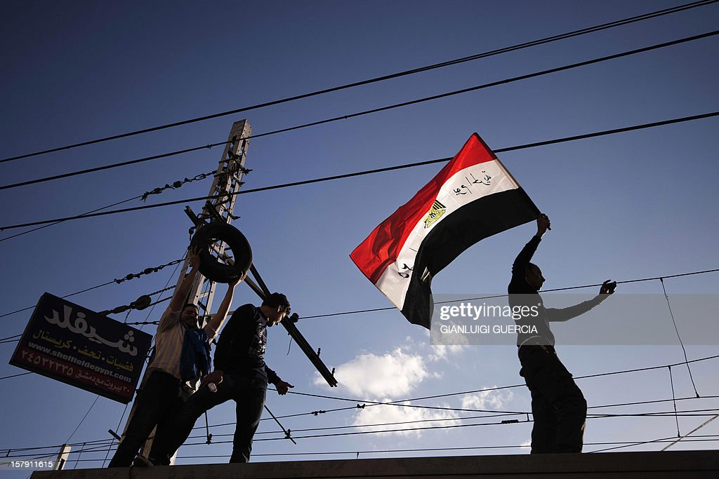 An Egyptian demonstrator waves his national flag as he walks with others on top of a trolley station near the presidential palace in Cairo on December 7, 2012 during a protest against a draft constitution and President Mohamed Morsi's sweeping powers decree. Thousands of protesters converged on the presidential palace in Cairo in a fresh bid to convince Morsi to give up what they see as dictatorial powers, and to postpone a referendum on a controversial new constitution.