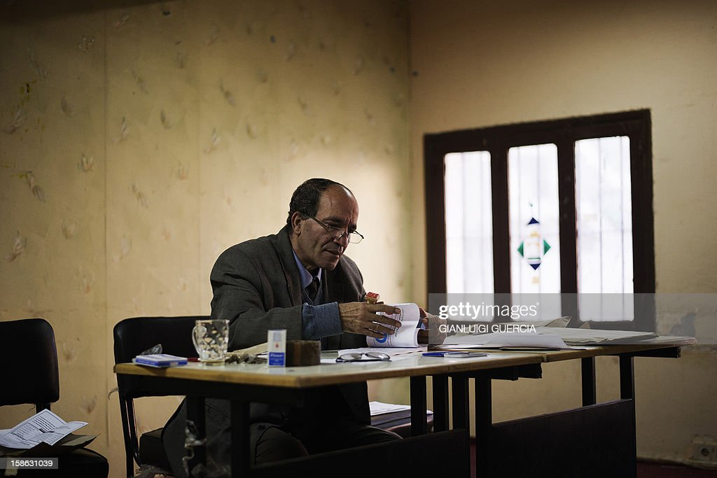 An Egyptian electoral official checks ballots during voting activities for the second round of a referendum on a new draft constitution in Giza, south of Cairo, on December 22, 2012. Egyptians are voting in the final round of a referendum on a new constitution championed by President Mohamed Morsi and his Islamist allies against fierce protests from the secular-leaning opposition.