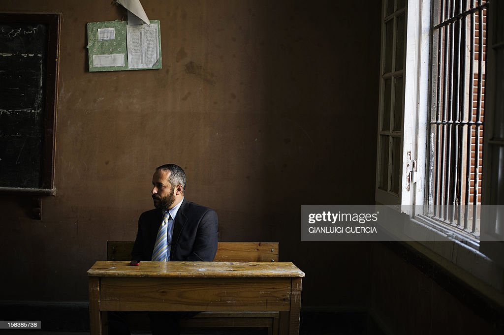 An Egyptian electoral official oversees voting activities as people cast their vote at a polling station in President Mohamed Morsi's hometown Zagazig in the Nile Delta on a new constitution supported by the ruling Islamists but bitterly contested by a secular-leaning opposition on December 15, 2012. Morsi's determined backing of the charter triggered the power struggle with the opposition, which is supported by judges who accuse the Islamists of overreaching. AFP PHOTO/GIANLUIGI GUERCIA