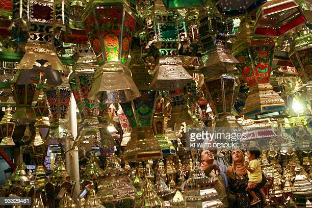 An Egyptian family looks to buy a 'Fanus Ramadan' a traditional lantern popular during the holy Muslim fasting month of Ramadan at a shop in elSayeda...