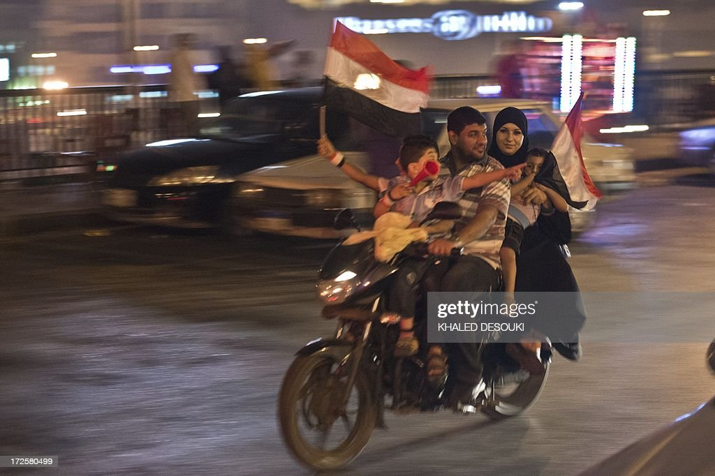 An Egyptian family on motorcycle celebrates in Cairo on July 3 2013 after a broadcast confirming that the army will temporarily be taking over from...