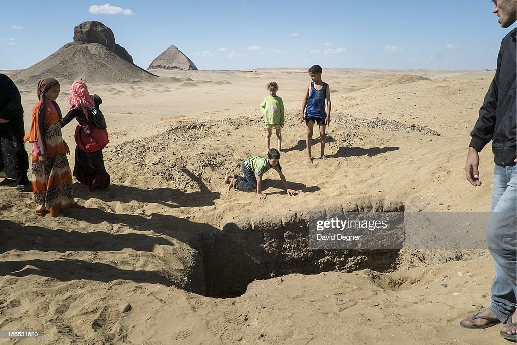 An Egyptian family visiting the pyramids of Dahshur explore new holes that have appeared nearby, on November 09, 2012, in Dahshur, Egypt. Artifact thieves have made new holes on the edge of Dahshur, digging beside the archeological sites of Sneferu's Pyramids. These include Sneferu's Red Pyramid, and Sneferu's Bent Pyramid. Since the revolution, Egyptian security forces haven't been guarding archeological sites as much as in the past.