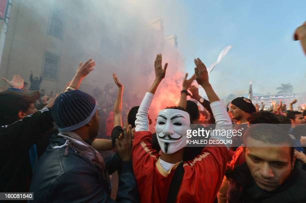 An Egyptian fan of AlAhly football club wearing a Guy Fawkes mask used by the Anonymous movement celebrates with other club supporters outside its...