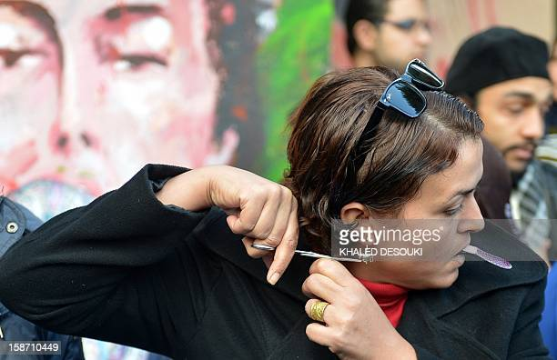 An Egyptian female protester cuts her hair during a demonstration mostly by Egyptian women against their country's new constitution draft on December...