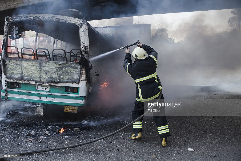 An Egyptian firefighter extinguishes a burning bus set alight during violent clashes between supporters of Egyptian President Mohammed Morsi and opposition demonstrators on April 19, 2013 in central Cairo, Egypt. Clashes broke out between Islamist protesters and opposition demonstrators, including members of the 'Black Block' - a group of masked protesters who oppose President Morsi and the Muslim Brotherhood - near Tahrir Square on Saturday afternoon. The two groups met after protests by opposing were held in different areas of central Cairo on Friday. (Photo by Ed Giles/Getty Images).