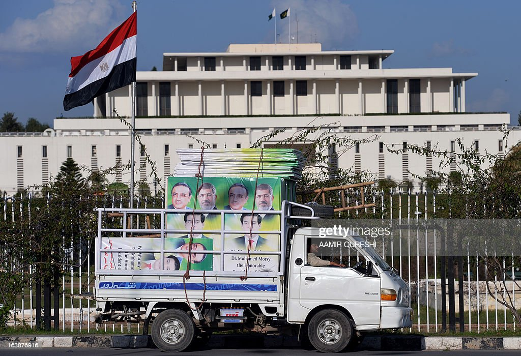 An Egyptian flag (L) flutters as a Pakistani driver parks a mini truck carrying welcoming banners with the photographs of Egyptian President Mohamed Morsi,(top-R), Pakistani President Asif Ali Zardari (top-L) and Prime Minister Raja Pervez Ashraf in front of the presidential palace in Islamabad on March 17, 2013. Morsi will visit Pakistan this week on a one-day state visit, Pakistan's Foreign Ministry said. Morsi is due in the country on March 18 by invitation of President Asif Ali Zardari and will bring with him 'a high-powered delegation', according to a ministry spokesman.