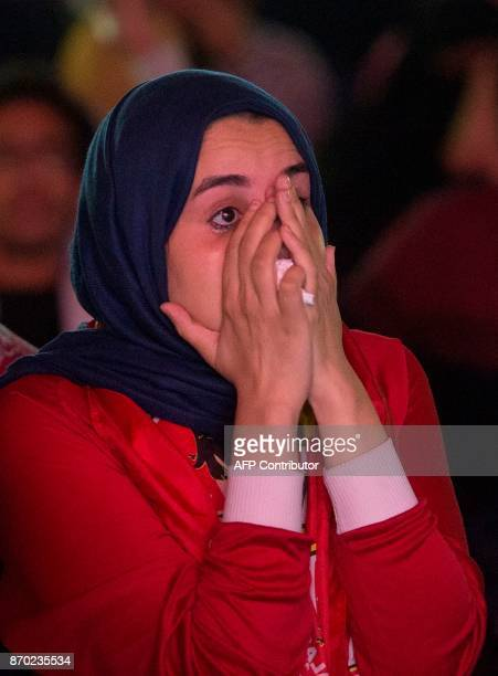 An Egyptian football fan reacts as people watch from the outskirts of Cairo the CAF Champions League final football match between Egypt's AlAhly and...