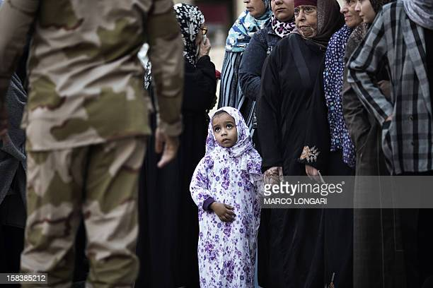 An Egyptian girl waits with relatives queuing to vote at a polling station in central Cairo on a new constitution supported by the ruling Islamists...