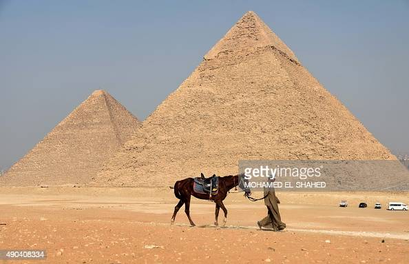 An Egyptian guide walks leading a horse at the Giza pyramids on the southern outskirts of Cairo on September 27 2015 AFP PHOTO / MOHAMED ELSHAHED