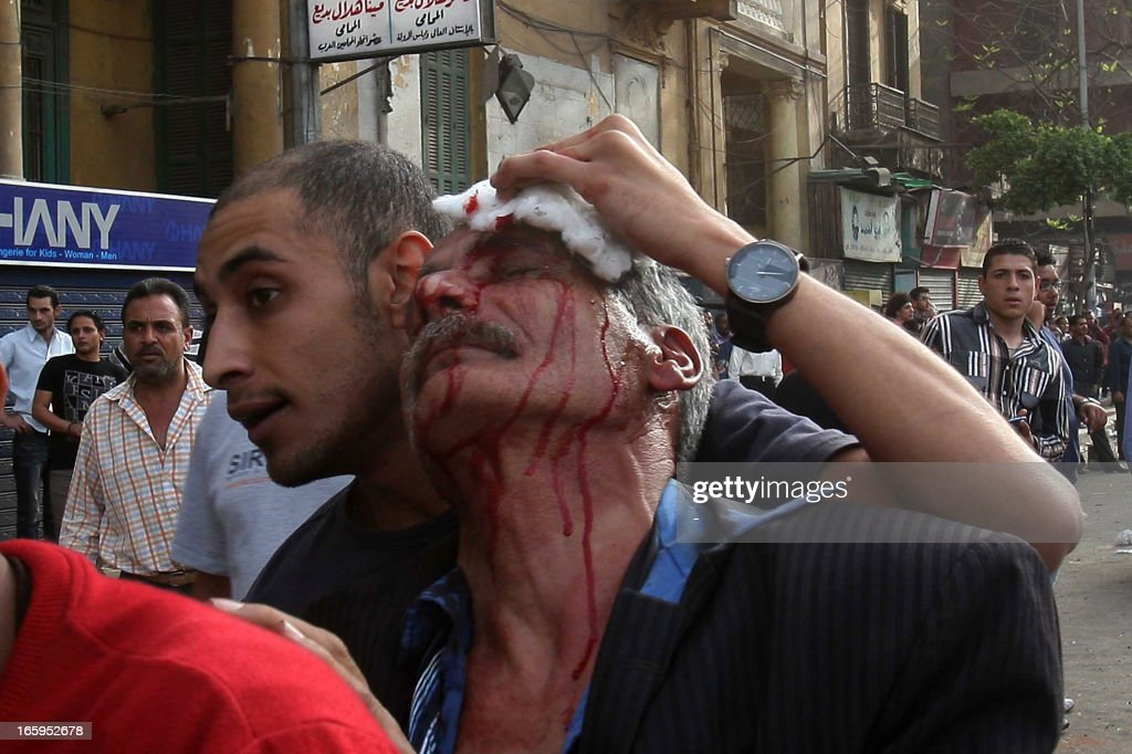 An Egyptian helps an injured man during sectarian clashes with Coptic Christians outside the Egyptian Coptic cathedral in Cairo's Abbassiya neighbourhood on April 7, 2013. One person died in the clashes after funeral prayers for four Christians during which angry Copts chanted against Egypt's Islamist President Mohamed Morsi, an official said.