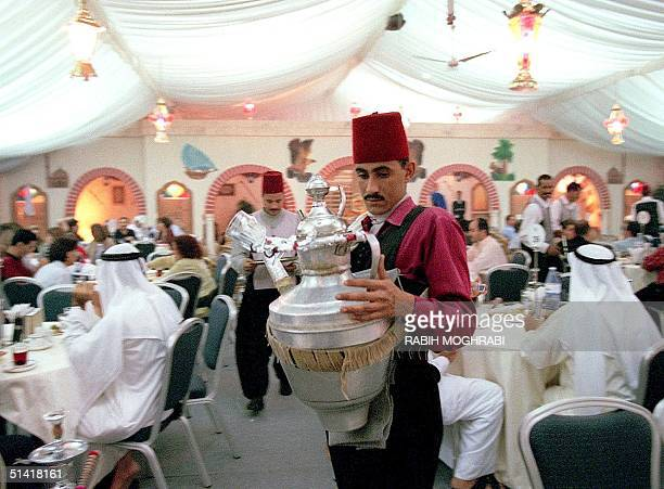 An Egyptian juice seller serves customers at a tent set up in Dubai for nighttime festivities late 02 January during the Moslem holy month of Ramadan...