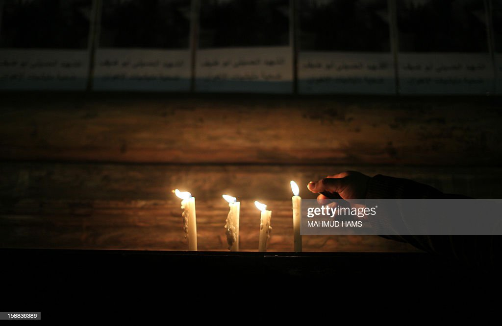 An Egyptian lights candles at the entrance of the Jounalist's Sydicate in Cairo on December 31, 2012, during a rally to commemorate the anniversary of the car bomb attack on the Al-Qiddissine (The Saints) church in the port city of Alexandria on January 1 2011. The attack killed at least 21 people, hitting Egypt's Christian community, the biggest in the Middle East. AFP PHOTO / MAHMUD HAMS