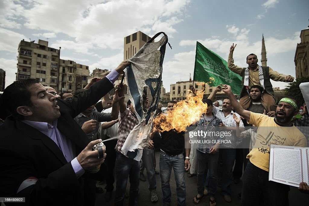 An Egyptian man burns an Israeli flag as another holds up the green Hamas movement flag during a demonstration in support of the Palestinian people and of Muslims around the world, on May 10, 2013 front of the Al-Ahzar mosque in Cairo. AFP PHOTO/GIANLUIGI GUERCIA