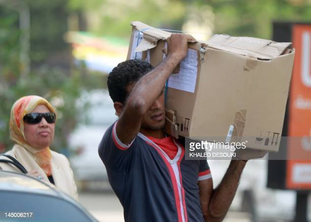 An Egyptian man carries a cardboard box containing voting ballots in the capital Cairo on May 22 a day before the first presidential election since...