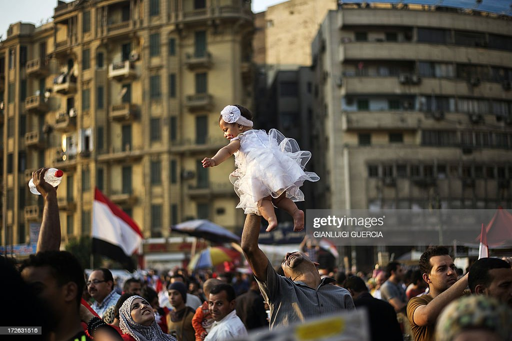 An Egyptian man carries his daughter in Egypt's landmark Tahrir square on July 4, 2013. Egypt's Muslim Brotherhood, from which ousted president Mohamed Morsi hails, denounced a new 'police state' after the arrest of Islamist leaders and the closure of satellite channels. AFP PHOTO/GIANLUIGI GUERCIA