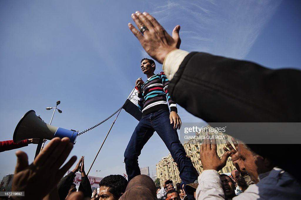 An Egyptian man delivers a speech as protesters gather in Cairo's landmark Tahrir square on November 30, 2012, to protest against a decree by President Mohamed Morsi granting himself broad powers that shield his decisions from judicial review. A coalition of leading dissidents has called for protest rallies, including in Cairo's Tahrir Square where three days ago tens of thousands vented their anger at Morsi's decree, denouncing him as a 'dictator' in the mould of toppled president Hosni Mubarak. AFP PHOTO/GIANLUIGI GUERCIA