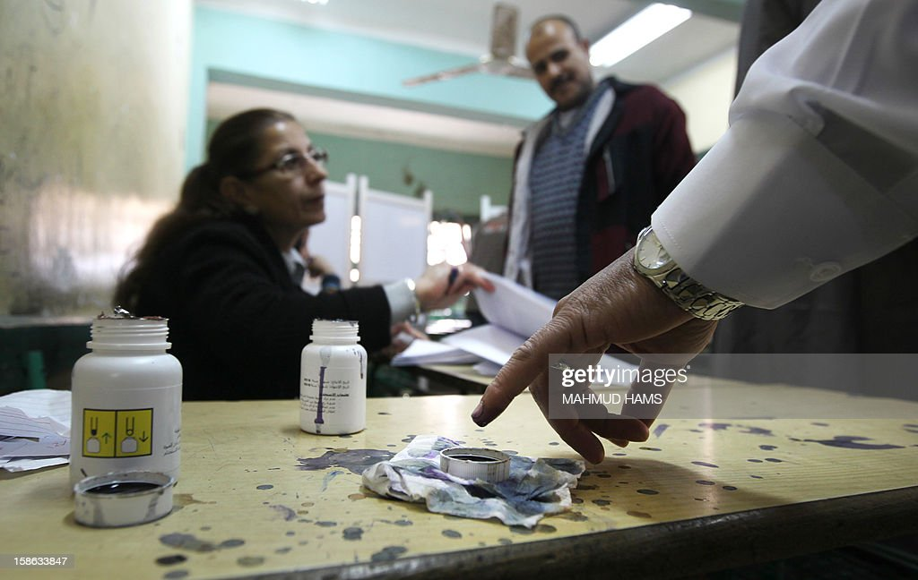 An Egyptian man dips his finger in ink after voting in the second round of a referendum on a new draft constitution in Giza, south of Cairo, on December 22, 2012. Egyptians are voting in the final round of a referendum on a new constitution championed by President Mohamed Morsi and his Islamist allies against fierce protests from the secular-leaning opposition.