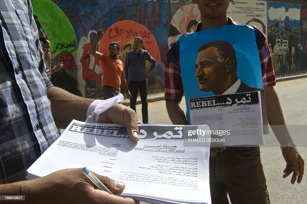 An Egyptian man distributes a sheet of Tamarod (rebellion) campaign try to collect signatures to demand the ouster of Egyptian President Mohamed Morsi and for early presidential elections in Cairo on May 17, 2013. Hundreds of people marched on Cairo's Tahrir Square calling for Morsi to resign and demanding early elections, AFP correspondents and local media reported. AFP PHOTO/KHALED DESOUKI