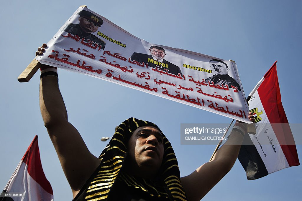An Egyptian man, dressed up as an Egyptian Pharaoh, holds a banner bearing a portrait of Egyptian President Mohamed Morsi flanked by portraits of Italian dictator Benito Mussolini and German Fuhrer Adolf Hitler in Cairo's landmark Tahrir square on November 30, 2012, to protest against a decree by President Mohamed Morsi granting himself broad powers that shield his decisions from judicial review. A coalition of leading dissidents has called for protest rallies, including in Cairo's Tahrir Square where three days ago tens of thousands vented their anger at Morsi's decree, denouncing him as a 'dictator' in the mould of toppled president Hosni Mubarak.